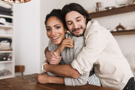 Handsome man dreamily embracing beautiful african american woman. Young international couple happily spending time together in cozy kitchen at home Banque d'images