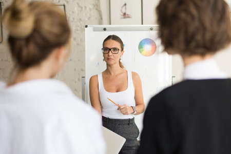 Young beautiful headmistress in eyeglasses standing near white board