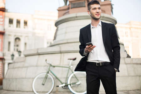 Young handsome businessman in classic black suit and white shirt with wireless earphones holding cellphone in hand dreamily looking aside with retro bicycle on background outdoor. Banque d'images