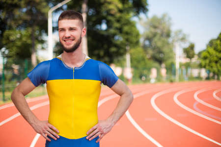 Young professional sportsman happily looking aside spending time on treadmill of stadium 版權商用圖片