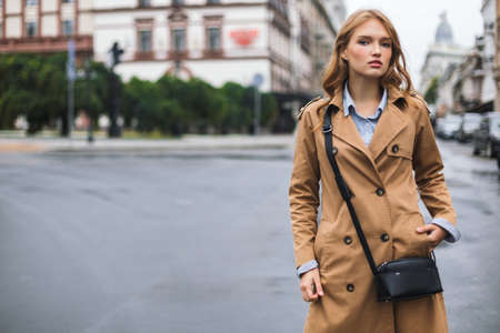 Young beautiful woman in trench coat with little black cross bag thoughtfully looking in camera spending time on cozy city street