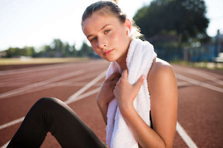 Beautiful girl in wireless earphones with white towel on neck dreamily looking in camera on racetrack of stadium