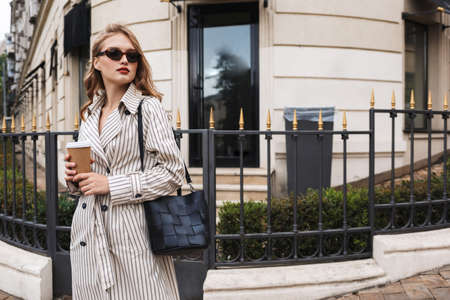 Beautiful girl in striped trench coat and sunglasses with black handbag holding coffee to go in hands, thoughtfully looking aside walking around cozy city street Imagens