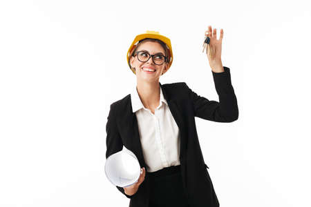 Young pretty businesswoman in eyeglasses and yellow helmet joyfully looking aside with plan and keys of new flat in hands over white background Stockfoto
