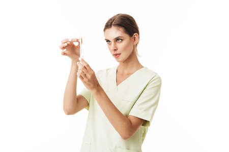 Young pretty nurse in uniform thoughtfully holding syringe in hands over white background Фото со стока
