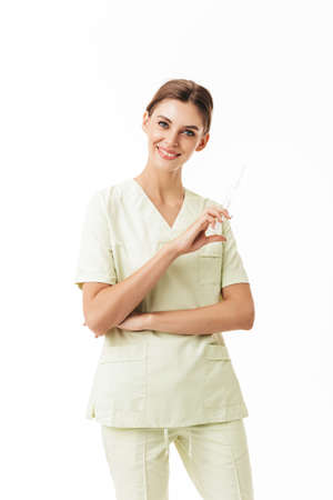 Young pretty smiling nurse in uniform holding syringe in hand happily looking in camera over white background