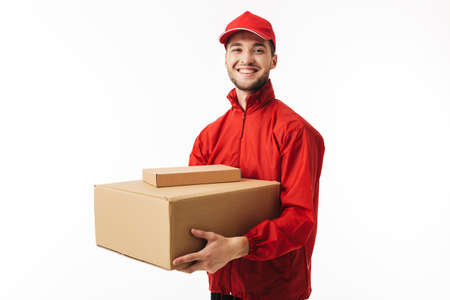 Young cheerful delivery man in red cap and jacket holding parcel in hands happily looking in camera over white background