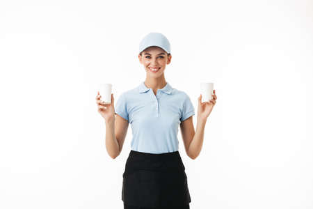 Beautiful smiling girl in blue polo T-shirt and cap holding in hands disposable cups for water happily looking in camera over white background