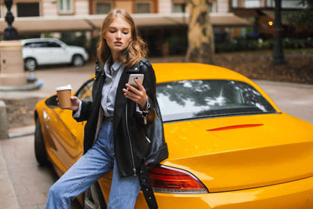 Young attractive woman in leather jacket leaning on yellow sport car holding cup of coffee to go in hand, thoughtfully using cellphone on city street 스톡 콘텐츠 - 146779316