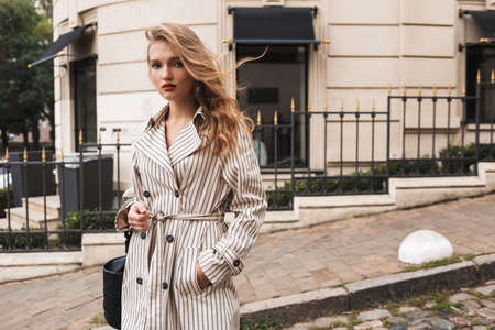 Beautiful pensive girl in striped trench coat with black handbag dreamily looking in camera walking around cozy city street