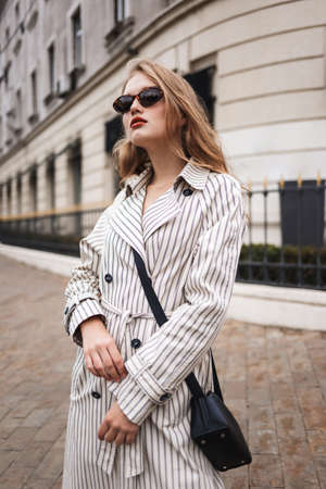 Young pensive woman in striped trench coat with little black cross bag thoughtfully looking aside walking around cozy city street