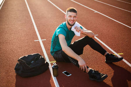 Young smiling man joyfully looking in camera with white towel on shoulder spending time on running track of stadium