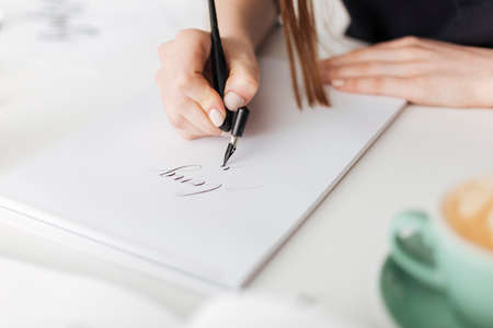 Close up photo of woman hands holding pen and writing beautiful notes on paper isolated. Stockfoto