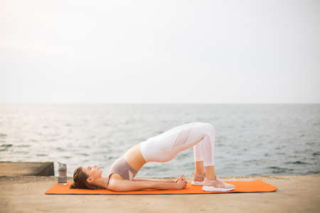 Young woman practicing yoga poses by the sea. Beautiful girl in sporty top and white leggings stretching on orange yoga mat with sea view on background