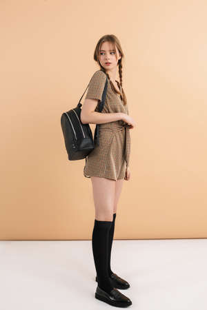 Young attractive girl with two braids in tweed jumpsuit and long black socks holding black backpack on shoulder thoughtfully looking aside over beige background