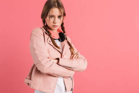 Young angry lady with two braids in leather jacket with headphones on neck holding hand together sadly looking in camera over pink background