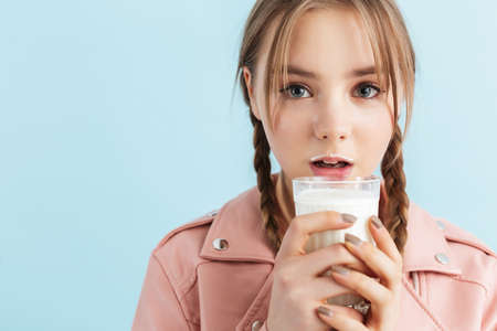 Young attractive girl with two braids in pink leather jacket with milk mustache holding glass in hand thoughtfully looking in camera over blue background Banque d'images