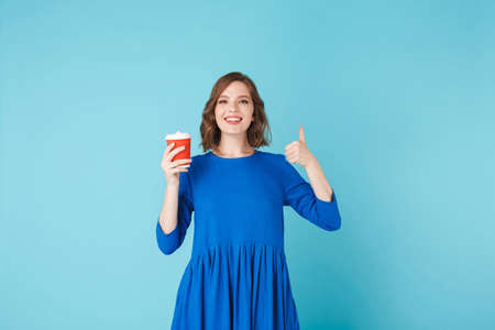 Portrait of young lady in dress standing with cup of coffee to go on over blue background. Pretty girl happily showing big thumb up gesture while looking in camera
