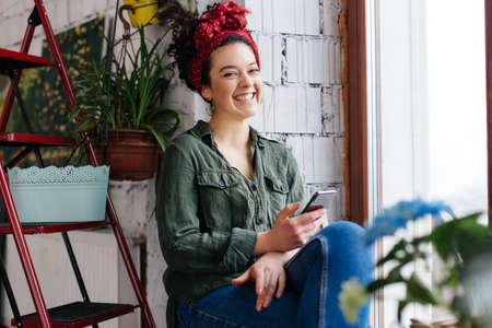 Young cheerful woman with dark curly hair sitting near ladder with flowers holding cellphone in hand happily looking in camera in modern cozy workshop