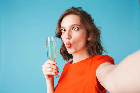 Portrait of young lady in dress standing with champagne and taking cute photos on over pink background.