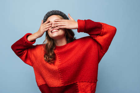 Beautiful smiling girl with wavy hair in hat and red sweater happily covering eyes with hands over blue background