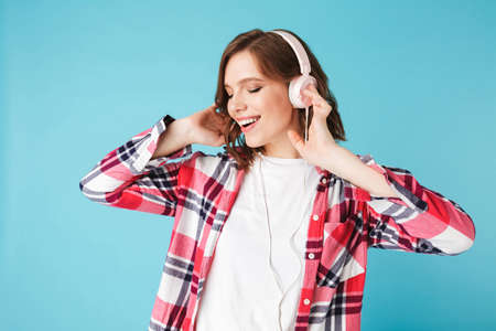 Portrait of young pretty lady in shirt dancing while listening music in headphones on over pink background.