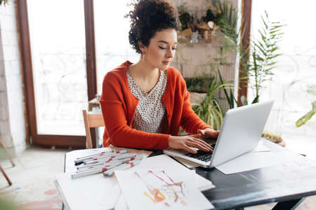 Young beautiful woman with dark curly hair sitting at the table, dreamily working on laptop with fashion illustration near in modern cozy workshop with big windows