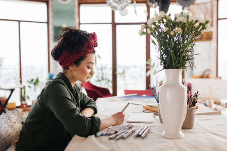 Young beautiful woman with dark curly hair sitting at the table dreamily drawing sketches spending time in cozy workshop with big windows Stockfoto