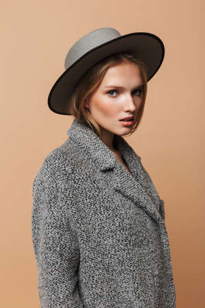 Young attractive woman with wavy hair in gray hat and coat thoughtfully looking in camera over beige background 版權商用圖片