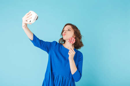 Beautiful lady in dress standing with lollipop and taking cute photo on her little camera on over blue background.