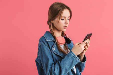 Young attractive dreamy girl with two braids in denim jacket with headphones thoughtfully using cellphone over pink background