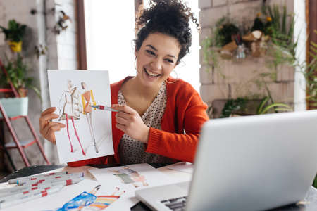 Young cheerful woman with dark curly hair sitting at the table, happily showing fashion illustration in laptop spending time in modern cozy workshop with big windows