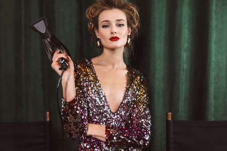 Young beautiful woman with wavy hairstyle and red lips in bright cocktail dress holding hair dryer in hand,, dreamily looking in camera over dark green background