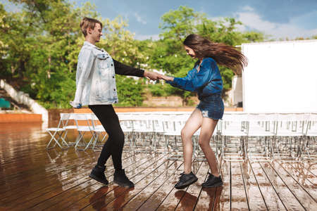 Young joyful couple happily dancing under rain on date in park . Beautiful couple spending time together with white chairs on background 版權商用圖片