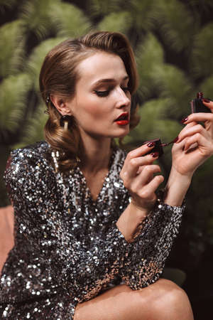 Young beautiful woman with wavy hairstyle and red lips in sequins dress dreamily painting nails spending time alone isolated