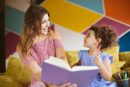Beautiful smiling mother with her little cute daughter happily looking at each other reading child book together on sofa at home