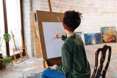 Young woman with dark curly hair from back sitting on chair thoughtfully drawing picture on canvas spending time in cozy art workshop alone