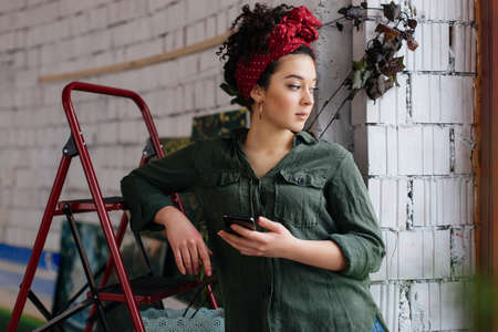 Young beautiful woman with dark curly hair leaning on ladder with cellphone in hand dreamily looking aside spending time in modern cozy workshop 版權商用圖片