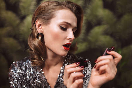 Close up young beautiful woman with wavy hairstyle and red lips in sequins dress and big earrings thoughtfully painting nails spending time alone indoor 版權商用圖片