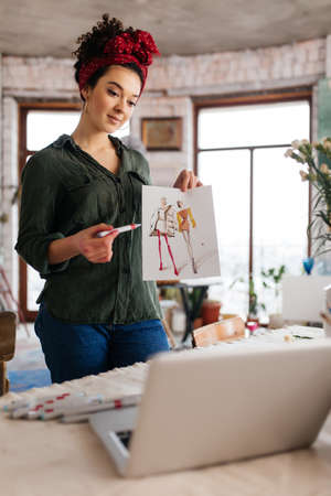 Young beautiful woman with dark curly hair standing near table, dreamily showing fashion sketch in laptop spending time in modern cozy workshop with big windows 版權商用圖片