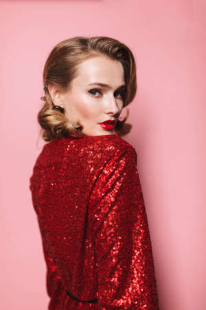 Young gorgeous woman with wavy hairstyle and red lips in bright dress from back dreamily looking in camera over pink background