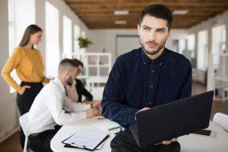 Young serious man with beard in shirt thoughtfully looking aside holding laptop in hands spending time in office with colleagues on background