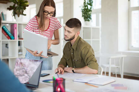 Young thoughtful man in shirt and woman in striped T-shirt and eyeglasses thoughtfully working together with laptop. Business people spending time at work in modern office