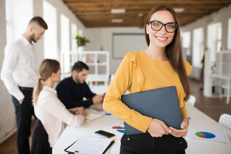 Young smiling business woman in eyeglasses happily looking in camera holding folder in hands in office with colleagues on background