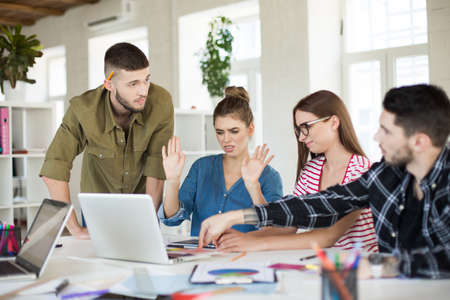 Group of young business people with laptop emotionally discussing work together. Upset men and women working in modern office