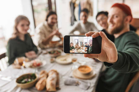Group of attractive international friends sitting at the table with food spending time together. Young colleagues joyfully taking photo on modern cellphone having lunch in cozy cafe