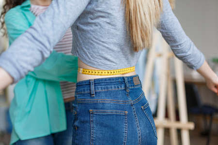 Close up designer measuring customer waist with tape in modern sewing workshop