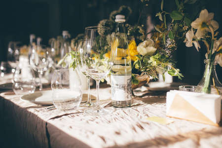 Wedding banquet. Table for guests, decorated with candles and flowers, served with cutlery and crockery and covered with a tablecloth.