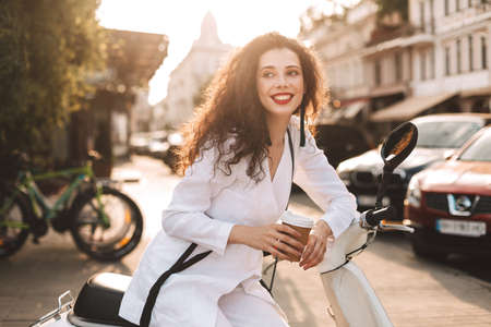 Pretty smiling lady with dark curly hair in white costume sitting on white moped with cup of coffee to go, and happily looking aside with beautiful city view on background