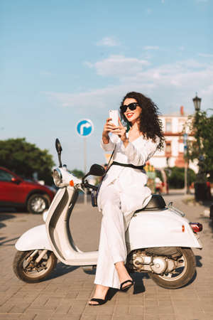 Young smiling woman with dark curly hair in white costume and sunglasses sitting on white moped, and happily taking photos on cellphone on street with city view on background